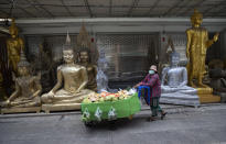 A fruit vendor wearing a protective mask to help curb the spread of the coronavirus pushes her cart past giant Buddhist statues for sale in Bangkok, Thailand, Thursday, May 27, 2021. (AP Photo/Sakchai Lalit)