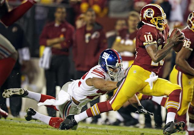 New York Giants defensive end Osi Umenyiora (72) reaches for Washington Redskins quarterback Robert Griffin III (10) during the first half of an NFL football game in Landover, Md., Monday, Dec. 3, 2012. (AP Photo/Evan Vucci)