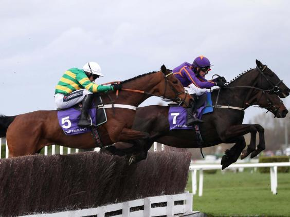 Champ ridden by jockey Barry Geraghty (left) on their way to wining the RSA Chase (PA)
