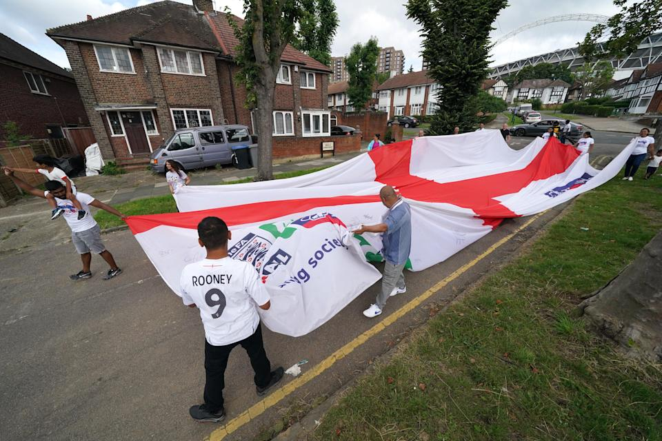 Local residents carry an official giant England Nationwide respect campaign flag from Neeld Crescent in Brent, where Raheem Sterling grew up, to Wembley Stadium, ahead of the Euro 2020 final (PA Wire)
