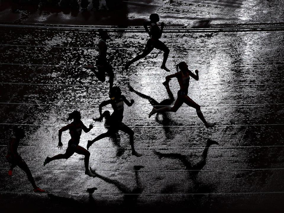 Silhouettes of track runners in the rain at the Tokyo Olympics.