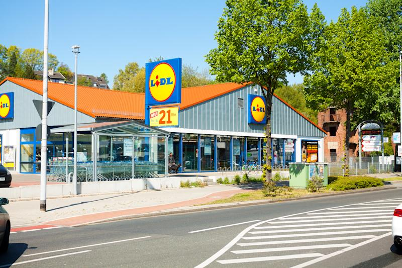 Mülheim, Germany - April 19, 2014: Capture of Lidl supermarket in Mülheim, Ruhrgebiet, View over street. A car is driving onto parking space. Outside of supermrket are people.