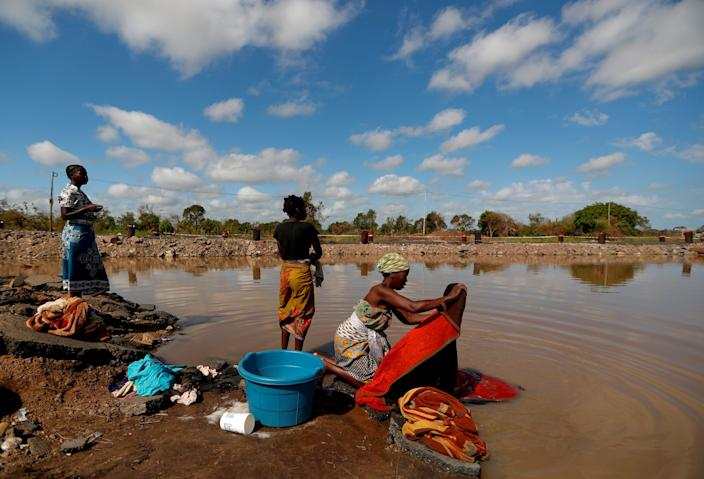 "Maria Jofresse, 25, speaks with her neighbors as they wash clothes in flood water in the aftermath of Cyclone Idai, next to the village of Cheia, which means ""Flood"" in Portuguese, near Beira, Mozambique, April 2, 2019. (Photo: Zohra Bensemra/Reuters)"