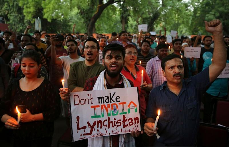 protesters shout slogans as they hold placards and candles during a protest condemning recent mob lynching of Muslim youth Tabrez Ansari in Jharkhand state, in New Delhi, India, Wednesday, June 26, 2019