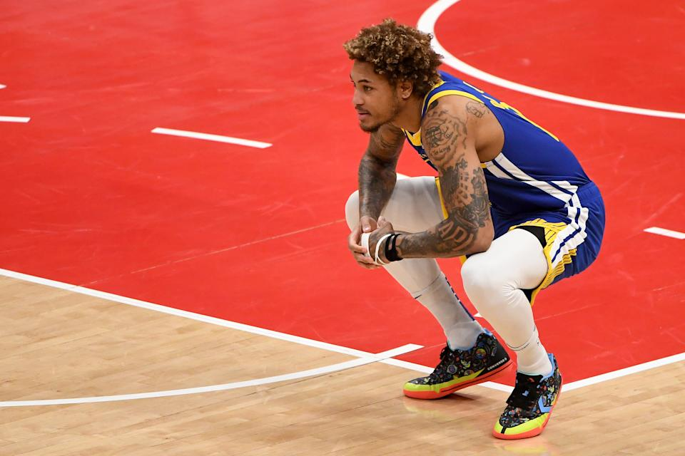 Kelly Oubre Jr. squats down and looks on during a game.