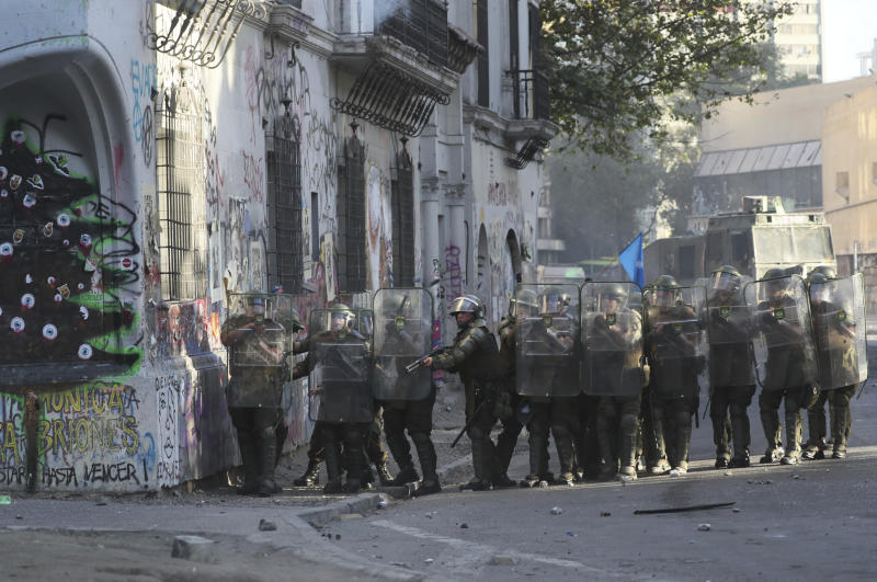 A police officer looks down the street after firing his shotgun during clashes with anti-government demonstrators in Santiago, Chile, Friday, Dec. 20, 2019. Chile marks a second full month of unprecedented social revolt that has not only altered the country's political landscape but also prompted a referendum on reforming the country's dictatorship-era. (AP Photo/Fernando Llano)