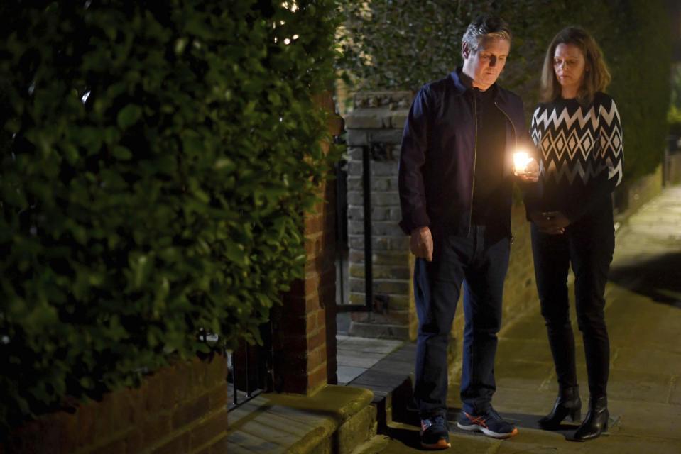 Labour leader Sir Keir Starmer and his wife Victoria hold a candle outside their home in north London, during a doorstep vigil for Reclaim These Streets, after the public vigil for Sarah Everard was officially cancelled, in London, Saturday, March 13, 2021. A serving British police officer accused of the kidnap and murder of a woman in London has appeared in court for the first time. Wayne Couzens, 48, is charged with kidnapping and killing of 33-year-old Everard, who went missing while walking home from a friend's apartment in south London on March 3. (Victoria Jones/PA via AP)