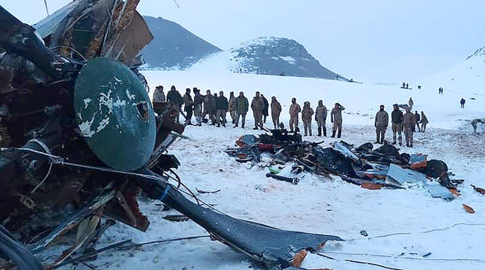 Soldiers and rescue workers stand around the wreckage after an army helicopter crashed in Bitlis, eastern Turkey, Thursday March 4, 2021. Turkey's Defense Ministry says a military helicopter has crashed, killing several soldiers on board and injuring others. News reports said the victims included an army corps commander. The ministry described the crash as an accident, but it wasn't immediately known what caused it. (IHA via AP )