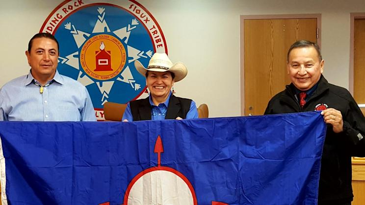 Grand Chief Stewart Phillip, right, and his wife Joan, centre, present the Union of B.C. Indian Chiefs flag to Standing Rock Sioux Tribal council chairman Dave Archambault II in September. Supplied photo.
