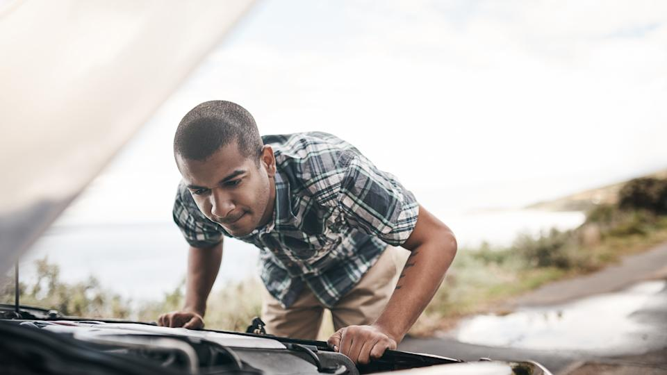 Cropped shot of a young man with his broken down car on the side of a road.