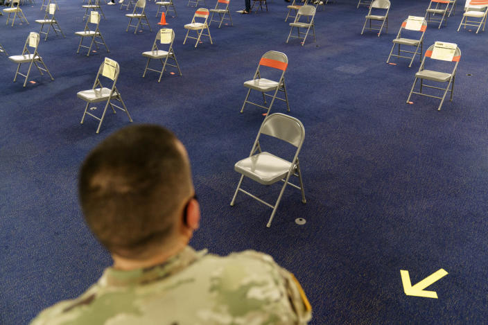 Rhode Island Army National Guard Sgt. Juan Gomez looks over the post inoculation waiting area at a coronavirus mass-vaccination site at the former Citizens Bank headquarters in Cranston, R.I., Thursday, June 10, 2021. The U.S. is confronted with an ever-growing surplus of COVID-19 vaccines, looming expiration dates and stubbornly lagging demand at a time when the developing world is clamoring for doses to stem a rise in infections. (AP Photo/David Goldman)