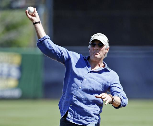 Actor Richard Gere throws out the ceremonial first pitch in a spring training baseball game between the Tampa Bay Rays and the New York Yankees in Tampa, Fla., Sunday, March 9, 2014. (AP Photo/Kathy Willens)