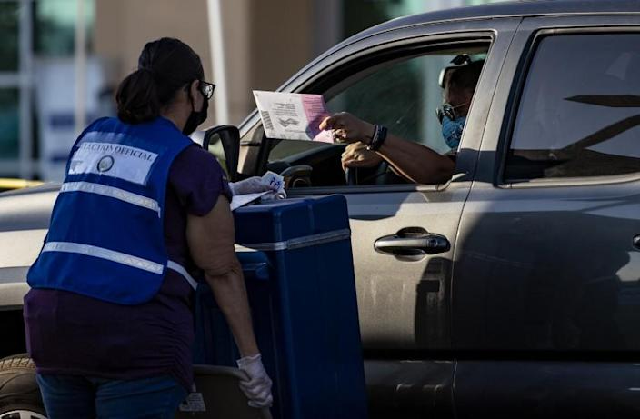 RIVERSIDE, CA - OCTOBER 30, 2020: A voter leaves his ballot during a drive-through ballot delivery at the voters' office on October 30, 2020 in Riverside, California. There was a constant line of cars until 5 pm closing time. (Gina Ferazzi / Los Angeles Times)