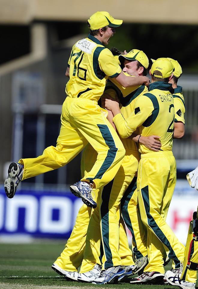 TOWNSVILLE, AUSTRALIA - AUGUST 11:  Joel Paris (obscured) celebrates taking the wicket of Daniel Bell-Drummond of England with team mates during the ICC U19 Cricket World Cup 2012 match between Australia and England at Tony Ireland Stadium on August 11, 2012 in Townsville, Australia.  (Photo by Ian Hitchcock-ICC/Getty Images)