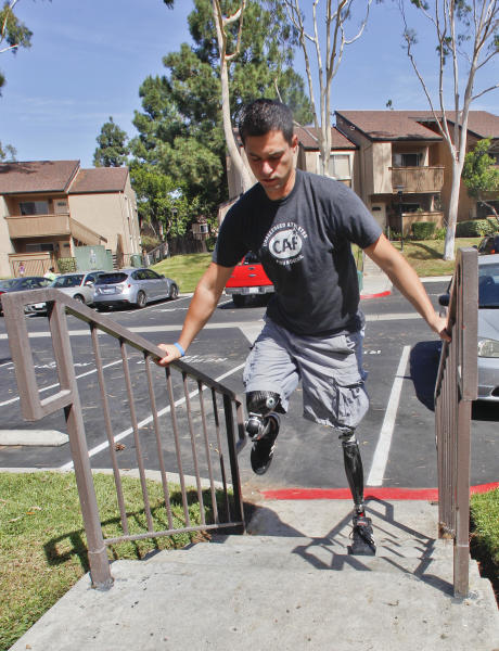 """FILE - In this Thursday, Oct. 4, 2012 file photo, U.S. Marine Cpl. Daniel Riley, 21, navigates the steps outside his apartment on his prosthetic legs in San Diego, Calif. Riley lost both legs to an IED in Afhganistan. Learning to walk on his prosthetic legs was """"like kicking a soccer ball in a swimming pool."""" Nearly 2,000 American troops have lost a leg, arm, foot or hand in Iraq or Afghanistan, and their sacrifices have led to advances in the immediate and long-term care of survivors, as well in the quality of prosthetics that are now so good that surgeons often chose them over trying to save a badly mangled leg. (AP Photo/Lenny Ignelzi)"""