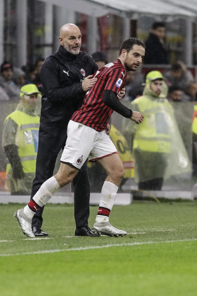 AC Milan's manager Stefano Pioli, left, and midfielder Giacomo Bonaventura during the Serie A soccer match between AC Milan and Napoli, at the San Siro stadium in Milan, Italy, Saturday, Nov. 23, 2019. (AP Photo/Luca Bruno)