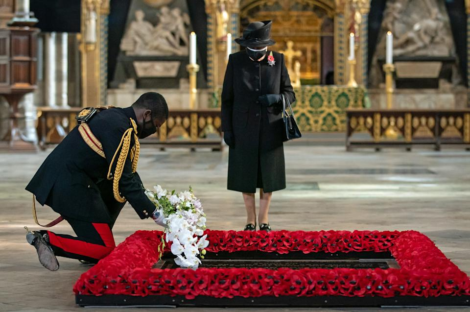 LONDON, ENGLAND - NOVEMBER 04: The Queen's Equerry, Lieutenant Colonel Nana Kofi Twumasi-Ankrah, places a bouquet of flowers at the grave of the Unknown Warrior on behalf of Queen Elizabeth II (centre) during a ceremony in Westminster Abbey to mark the centenary of the burial of the Unknown Warrior on November 4, 2020. The grave of the Unknown Warrior is the final resting place of an unidentified British serviceman who died on the battlefields during the First World War and whose body was brought from Northern France and buried at Westminster Abbey on 11th November 1920. (Photo by Aaron Chown - WPA Pool/Getty Images)
