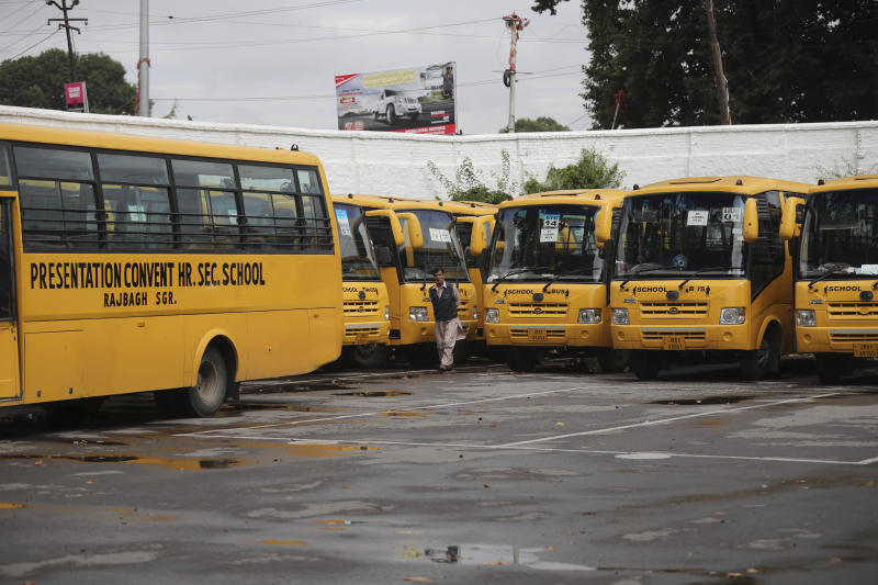 A staff member walks near buses parked inside the premises of a deserted school compound in  Srinagar, Indian controlled Kashmir, Monday, Aug. 19, 2019. Restrictions continue in much of Indian-administered Kashmir, despite India's government saying it was gradually restoring phone lines and easing a security lockdown that's been in place for nearly two weeks. (AP Photo/Mukhtar Khan)