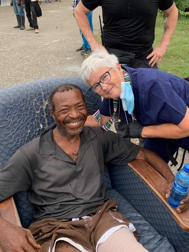Carolyn Davies, a nurse from Amherstburg, Ont., with a patient who suffered broken legs in the earthquake earlier this month. Davies is a volunteer and team member with Canadian Medical Assistance Teams (CMAT), a disaster relief organization.  (Submitted by Carolyn Davies - image credit)