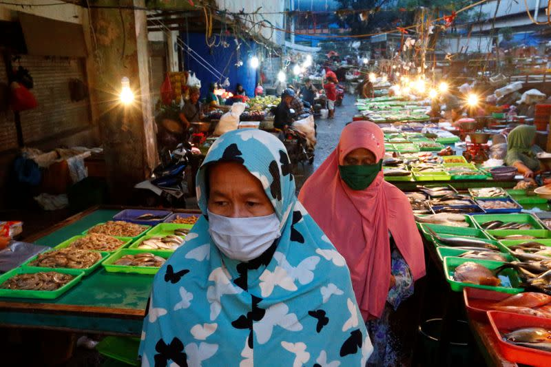Women wearing protective face masks as a preventive measure against the coronavirus disease (COVID-19) walk at a traditional market in Jakarta