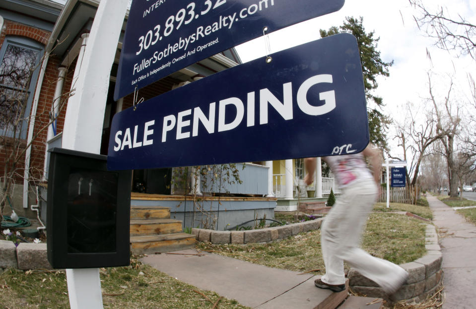 In this Saturday, March 17, 2012, photo, an unidentified woman passes by a pending sale sign outside home on the market in south Denver. A gauge of Americans who signed contracts to buy homes fell in April from nearly a two-year high in the previous month. The decline was the biggest in a year, but sales are still well ahead of last year's level for the same month, suggesting the housing market is improving slowly. (AP Photo/David Zalubowski)