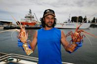 Fisherman Michael Vinci sells live western rock lobsters from his boat. The public has responded enthusiastically to the boat sales, queuing in the heat to buy directly on the quay in Fremantle