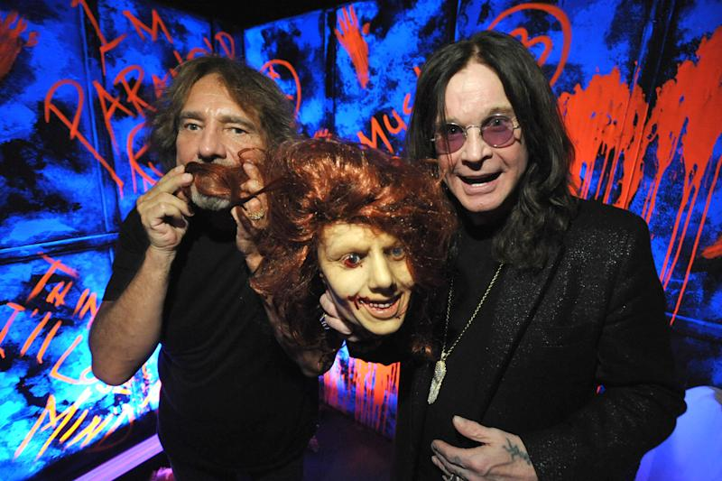 """In this Tuesday, Sept. 17, 2013 photo, Geezer Butler, left, and Ozzy Osbourne pose with props at the """"Black Sabbath: 13 3D"""" maze at Universal Studios Halloween Horror Nights, in Universal City, Calif. Several spooks at this year's Halloween Horror Nights are hyping new releases from the entertainment industry. Besides """"13"""" from Sabbath, there's a """"scare zone"""" populated by actors dressed as the nasty Chucky doll from the direct-to-DVD sequel """"Curse of Chucky,"""" and a new maze incorporating supernatural elements from the """"Insidious"""" films. (Photo by John Shearer/Invision/AP)"""