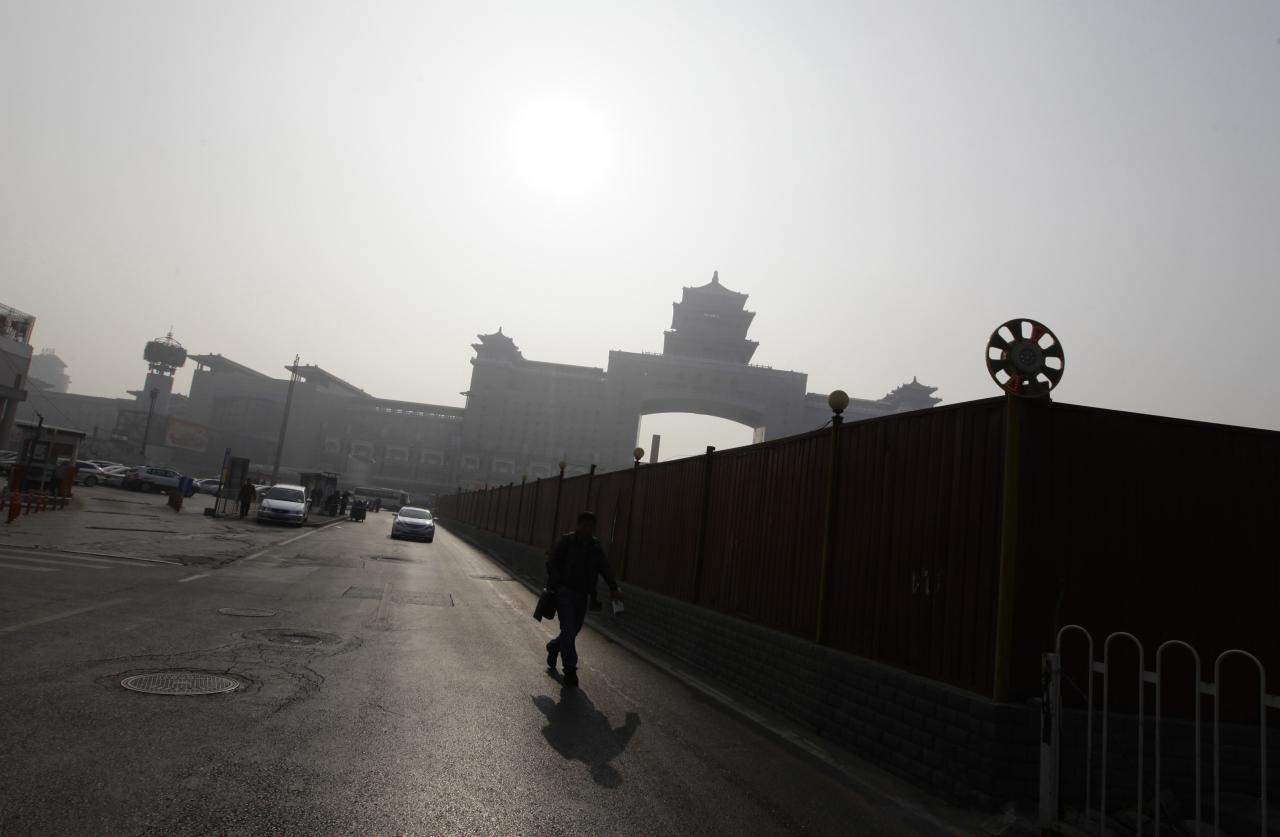 """A man walks near the Beijing West Railway Station on a hazy day in Beijing, January 17, 2014. Beijing's mayor pledged on Thursday to cut coal use by 2.6 million tonnes and set aside 15 billion yuan ($2.4 billion) to improve air quality this year as part of the city's """"all-out effort"""" to tackle air pollution, state news agency Xinhua said. REUTERS/Jason Lee (CHINA - Tags: ENVIRONMENT POLITICS)"""