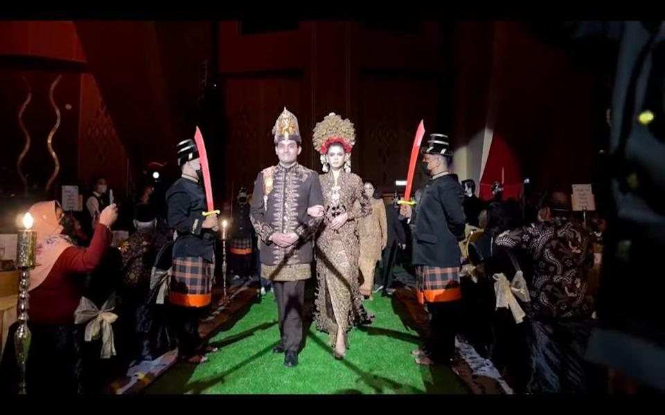 Newly-weds Tengku Muhammed Hafiz Adnan and Oceane Cyril Alagia enter the banquet hall as masked men in traditional Javanese garb stand guard.