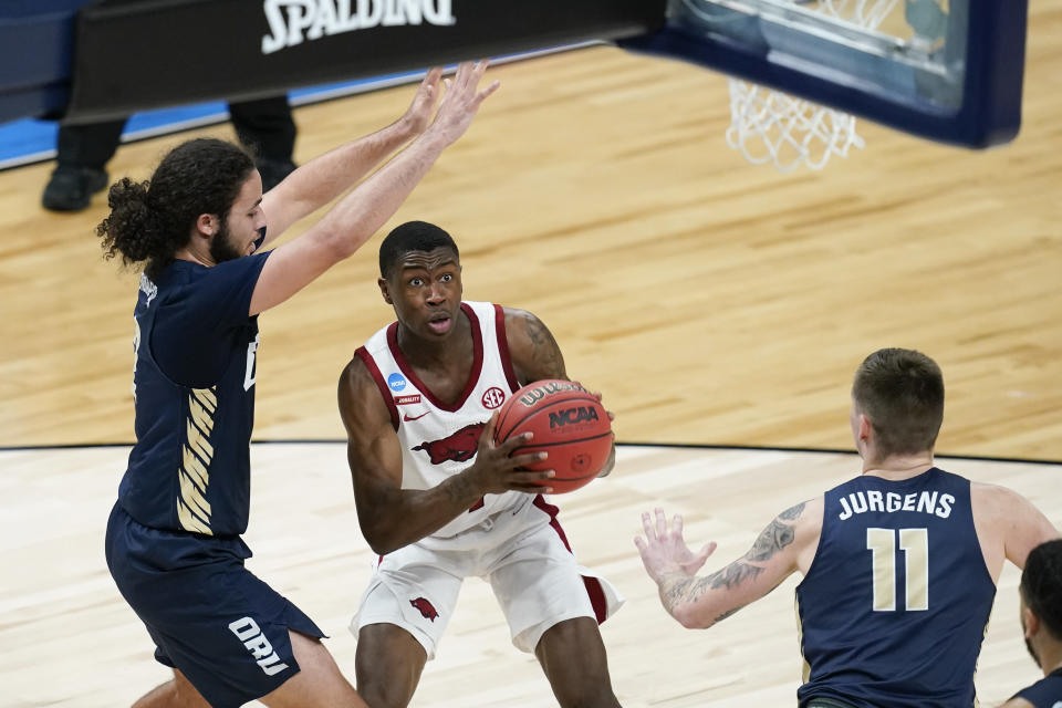 Arkansas guard Davonte Davis, center, drives to the basket between Oral Roberts guard Kareem Thompson, left, and guard Carlos Jurgens (11) during the second half of a Sweet 16 game in the NCAA men's college basketball tournament at Bankers Life Fieldhouse, Saturday, March 27, 2021, in Indianapolis. Arkansas won 72-70. (AP Photo/Darron Cummings)