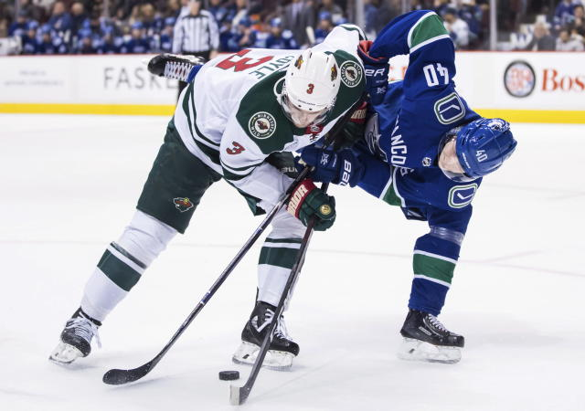 Minnesota Wild's Charlie Coyle, left, and Vancouver Canucks' Elias Pettersson, of Sweden, vie for the puck during the first period of an NHL hockey game in Vancouver, British Columbia, Tuesday Dec. 4, 2018. (Darryl Dyck/The Canadian Press via AP)