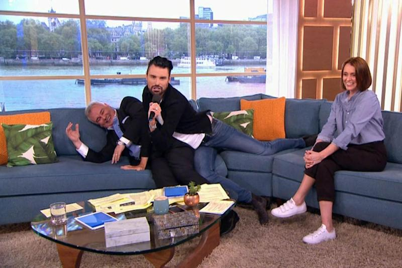 Raunchy: Rylan Clark-Neal writhes around on Eamonn Holmes as Keeley Hawes looks on (ITV)