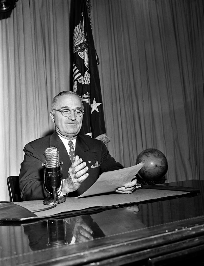 "FILE - In this Sept. 1, 1945, file photo President Harry Truman broadcasts his message on the formal surrender of Japan from the White House in Washington. Truman called on Congress in 1945 to create a national insurance program for those who pay voluntary fees, saying medical care is a right of all Americans. The American Medical Association denounces the idea as ""socialized medicine."" Truman tries for years but can't get it passed.  (AP Photo/File)"