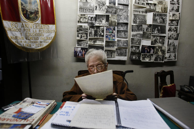 """In this Nov. 26, 2012 photo, journalist and radio host Maria Julia Venegas, better known as Maruja Venegas, 97, reads during an interview at her home in Lima, Peru. Venegas who began broadcasting """"Radio Club Infantil,"""" a show for Peru's children in the golden age of radio and World War II, has earned a citation from Guinness World Records as the globe's longest-running radio personality. (AP Photo/Karel Navarro)"""
