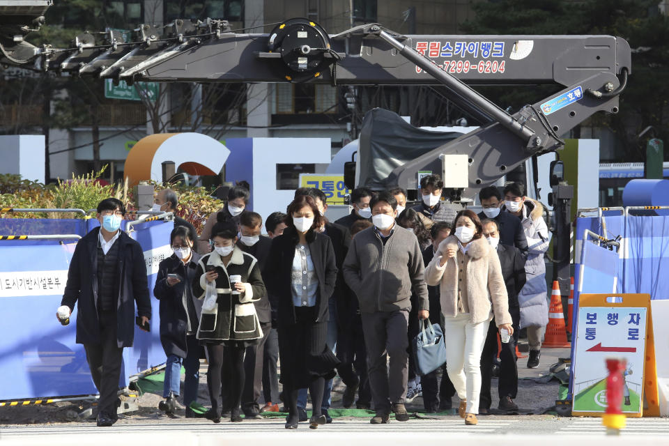 People wearing face masks as a precaution against the coronavirus cross a road in Seoul, South Korea, Friday, Nov. 27, 2020. South Korea's daily virus tally hovered above 500 for the second straight day, as the country's prime minister urged the public to stay home this weekend to contain a viral resurgence. (AP Photo/Ahn Young-joon)