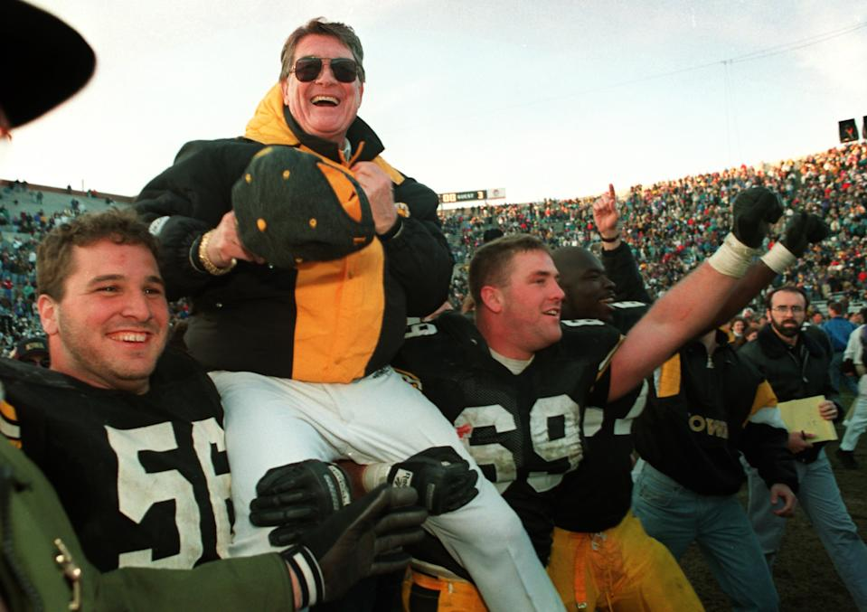 ** FILE ** Iowa football coach Hayden Fry is carried off the field after his team defeated Minnesota giving him his 200th career victory in this Nov. 20, 1993 file photo in Iowa City, Iowa. Fry, who retired after the 1998 season, was selected Monday, March 24, 2003, to the College Football Hall of Fame. (AP Photo/Charlie Neibergall)
