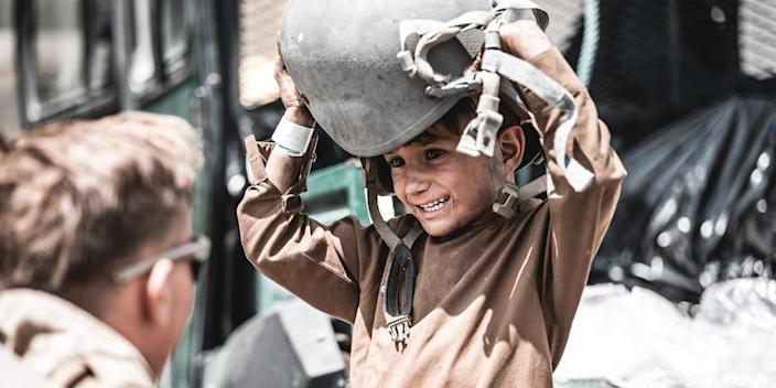 A Marine assigned to Special Purpose Marine Air-Ground Task Force - Crisis Response - Central Command hands a helmet to a child awaiting evacuation at Hamid Karzai International Airport, Afghanistan, Aug. 22, 2021