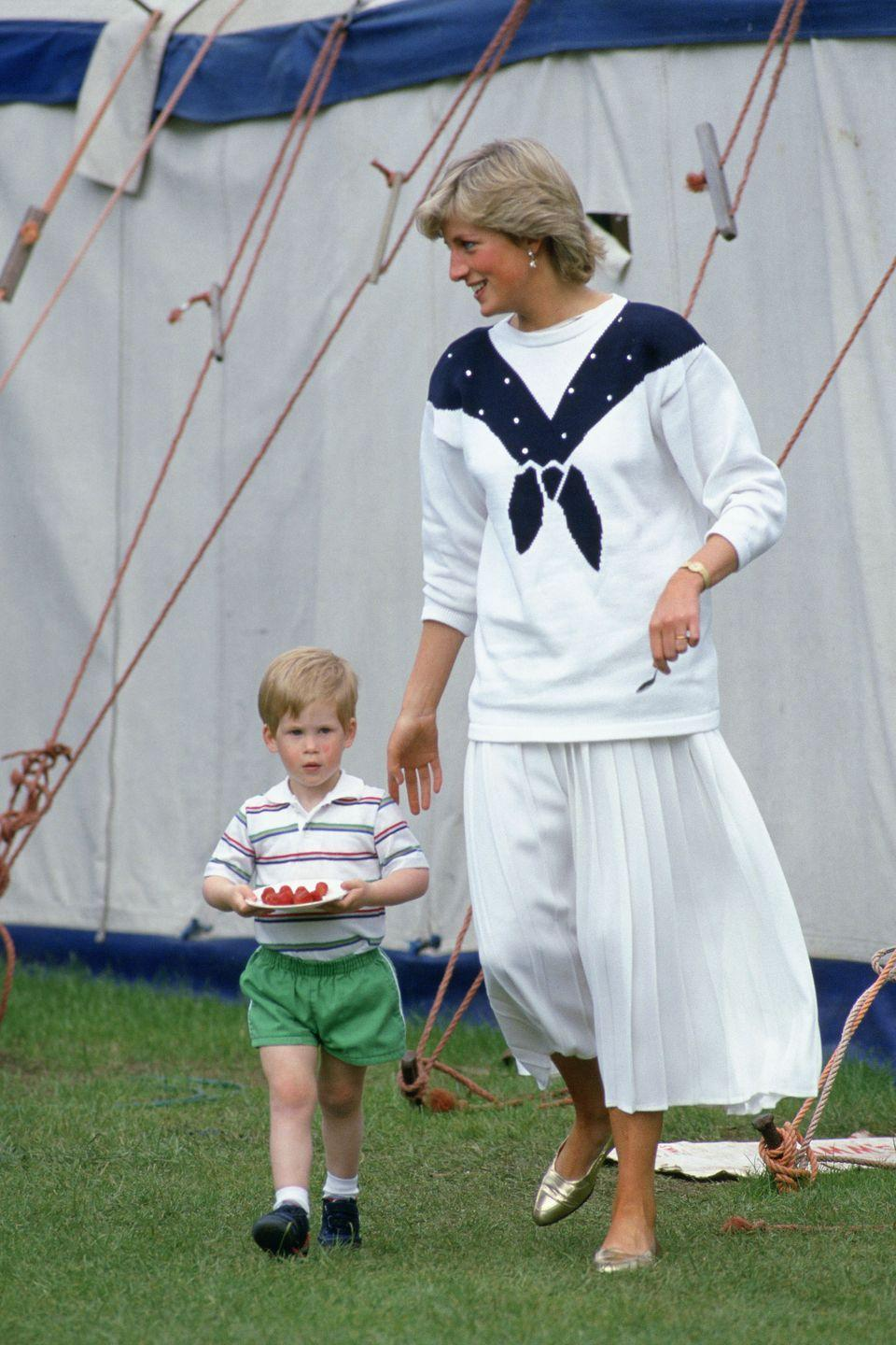 <p>In a sweater by Roland Klein and skirt by Jasper Conran while helping Prince Harry carry a plate of strawberries in Windsor.</p>