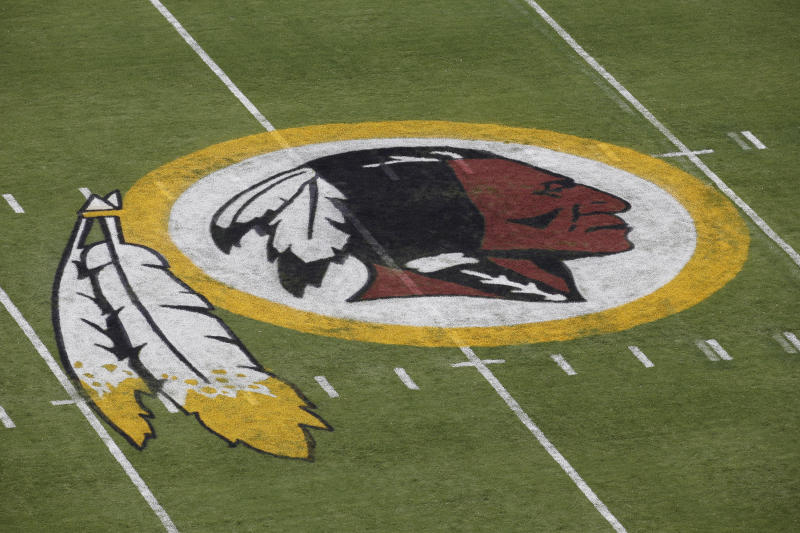 """FILE - In this Aug. 7, 2014 file photo, the Washington Redskins NFL football team logo is seen on the field before an NFL football preseason game against the New England Patriots in Landover, Md. The recent national conversation about racism has renewed calls for the Washington Redskins to change their name. D.C. mayor Muriel Bowser called the name an """"obstacle"""" to the team building its stadium and headquarters in the District, but owner Dan Snyder over the years has shown no indications he'd consider it. (AP Photo/Alex Brandon, File)"""