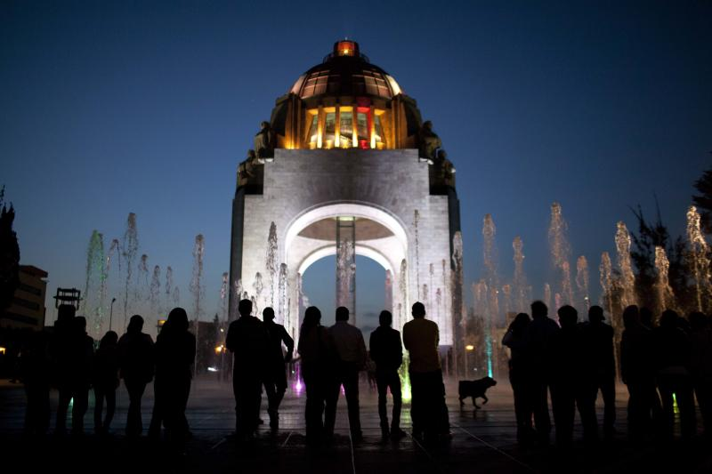 Pedestrians stand in front of the Arch of the Revolution monument in Mexico City, Wednesday, Dec. 26, 2012. The once-neglected plaza with an Arc de Triumph-style monument to Mexico's 1910 revolution has been remade from a homeless encampment to a place where families visit and children run through spurts of water gushing out of the pavement. The copper dome of what started out as the congressional rotunda is newly polished and gleaming. Mexico City's government is trying to transform one of the world's largest cities by beautifying public spaces, parks and monuments. (AP Photo/Alexandre Meneghini)