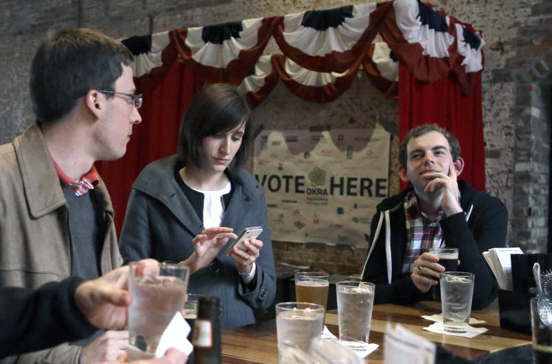 In this Dec. 13, 2013 photo, Jesse Mello, left, Erin Holt, center, and Matt Pankey enjoy drinks at The Original OKRA Charity Saloon in Houston. The gives 100 percent of its profits to charity and is set to donate more than $300,000 after its first year.(AP Photo/Pat Sullivan)