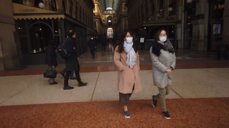 People wearing protective masks walk through the Galleria Vittorio Emanuele shopping centre during rush hour in Milan