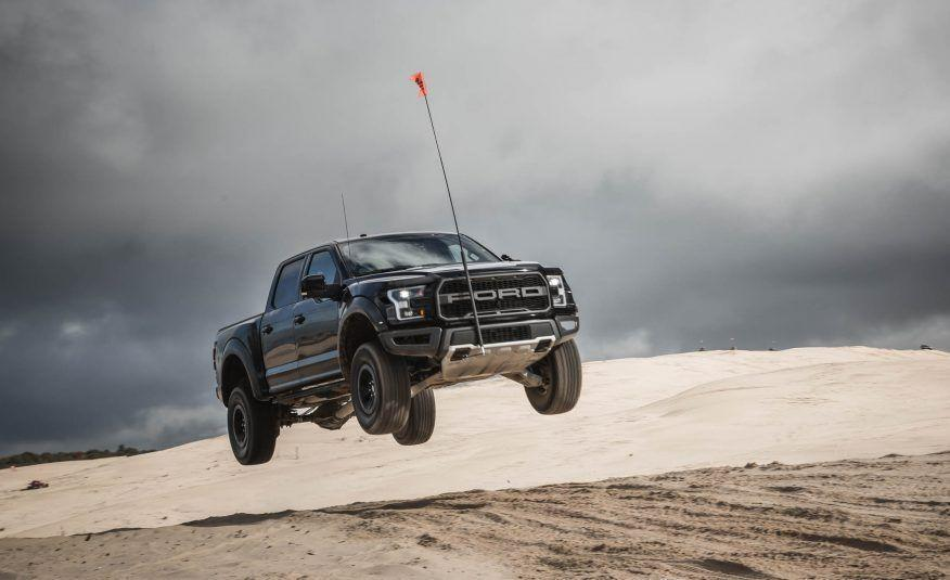 """<p>Does this shot look familiar? It should, because that's the same sand mound off which we launched the Tacoma TRD Pro. It's at Michigan's Silver Lake Sand Dunes park. We tested the Tacoma and the F-150 there at the same time but under orders from Ford we weren't allowed to share <a href=""""http://www.caranddriver.com/reviews/2017-ford-f-150-raptor-crew-cab-test-review"""" rel=""""nofollow noopener"""" target=""""_blank"""" data-ylk=""""slk:our Raptor experience"""" class=""""link rapid-noclick-resp"""">our Raptor experience</a> until about a month later. We found that, with much more horsepower and even beefier suspension components than the Toyota, the Ford pickup could safely carry far more speed over this jump, which explains why the Raptor made it much higher.</p>"""