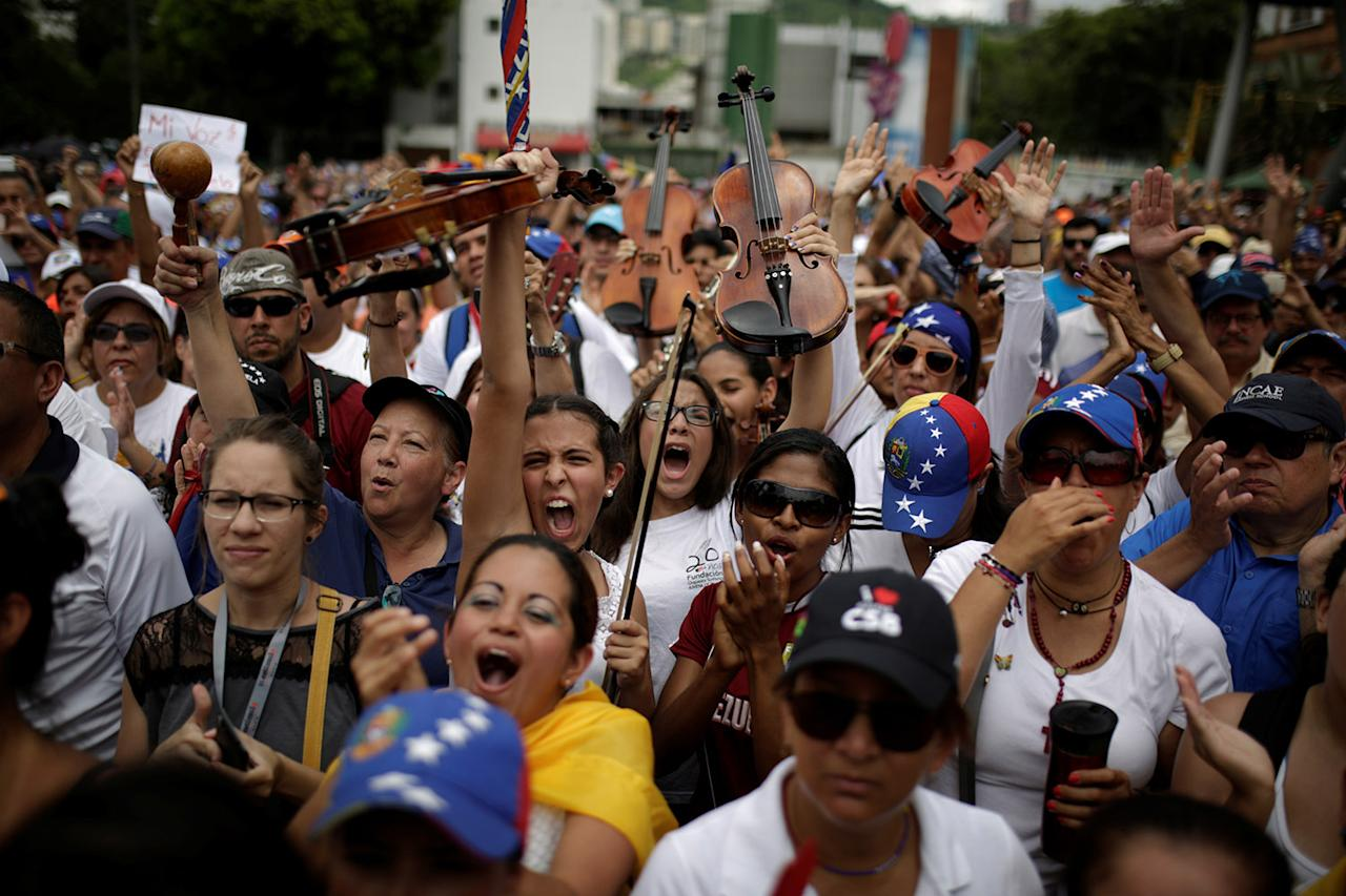 <p>Young musicians raise their violins during a gathering to pay homage to victims of violence during the protest against Venezuela's President Nicolas Maduro's government in Caracas, Venezuela, May 7, 2017. (Photo: Marco Bello/Reuters) </p>