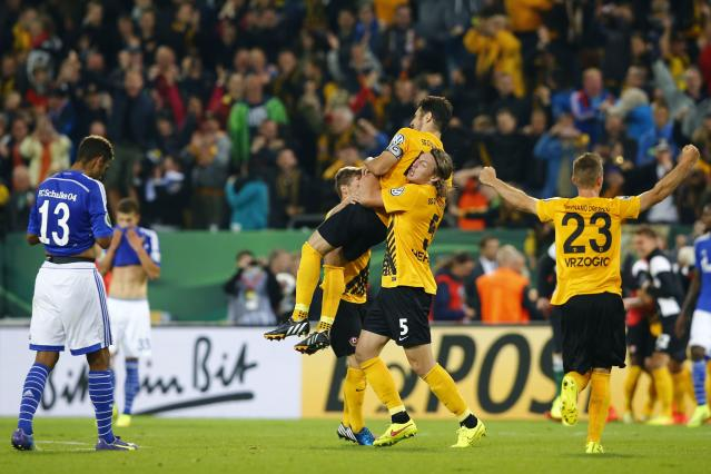 Dynamo Dresden players (R) celebrate after they defeated Schalke 04 during their German soccer cup (DFB Pokal) match in Dresden August 18, 2014. REUTERS/Thomas Peter (GERMANY - Tags: SPORT SOCCER) DFB RULES PROHIBIT USE IN MMS SERVICES VIA HANDHELD DEVICES UNTIL TWO HOURS AFTER A MATCH AND ANY USAGE ON INTERNET OR ONLINE MEDIA SIMULATING VIDEO FOOTAGE DURING THE MATCH