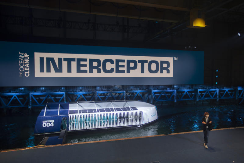 Young Dutch inventor Boyan Slat, right, unveils the Interceptor in Rotterdam, Netherlands, Saturday, Oct. 26, 2019. Slat is taking his effort to clean up floating plastic from the Pacific Ocean to rivers, using the Interceptor, a new floating device to catch garbage before it reaches the seas. (AP Photo/Peter Dejong)