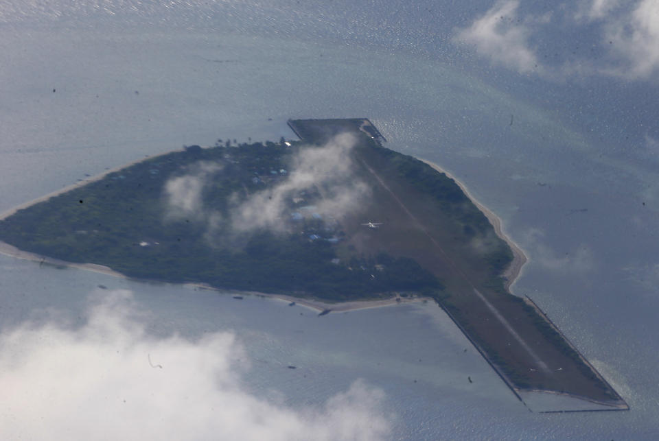 FILE PHOTO: This April 21, 2017 photo taken from a C-130 transport plane with Defense Chief Delfin Lorenzana and Armed Forces Chief Gen. Eduardo Ano shows Thitu Island off the South China Sea. (AP Photo/Bullit Marquez, File)