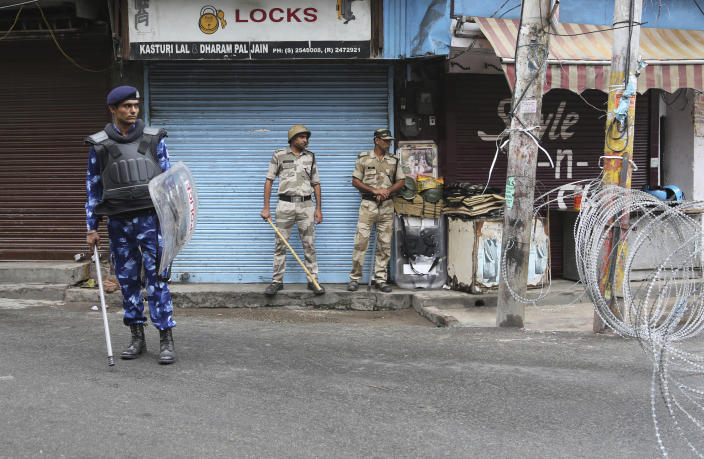 Security personnel stand guard in in Jammu, India, Friday, Aug. 9, 2019. The restrictions on public movement throughout Kashmir have forced people to stay indoors and closed shops and even clinics. All communications and the internet have been cut off. Prime Minister Modi said late Thursday the situation in the region would return to normal gradually. (AP Photo/Channi Anand)