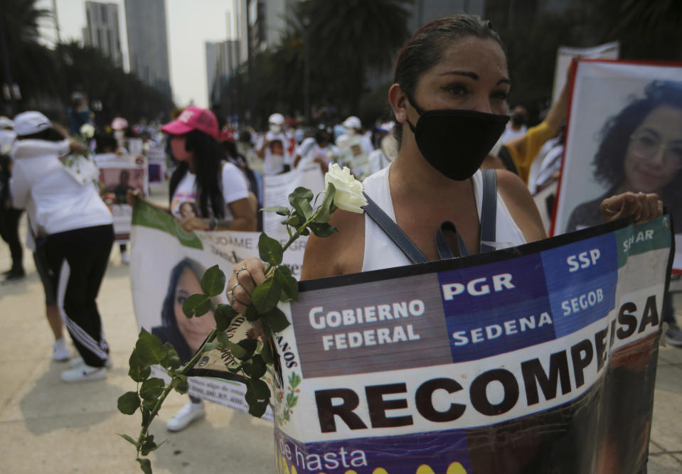 """A person holds the Spanish message """"Compensation"""" for information that would lead to the finding of a missing person, during a march in remembrance of those who have disappeared, on Mother's Day in Mexico City, Monday, May 10, 2021. (AP Photo/Fernando Llano)"""