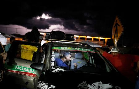 Venezuelan people are pictured inside a taxi before traveling towards Boa Vista city, after checking their passports or identity cards at the Pacaraima border control, Roraima state, Brazil August 19, 2018.  REUTERS/Nacho Doce